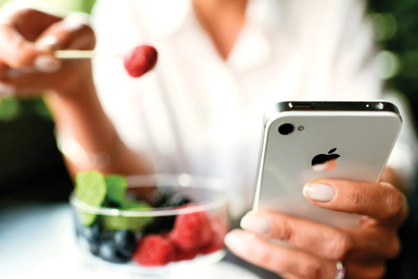 Woman eating fruits dessert with iPhone 4s in hands