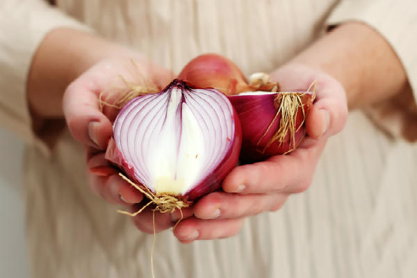 man holding a red onion